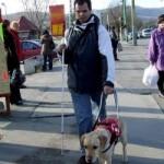 Egy vak férfi vakvezető kutyájával sétál az utcán.