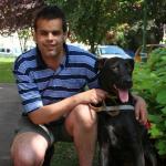 Egy fiatal férfi térdel a vakvezető kutyája mellett.