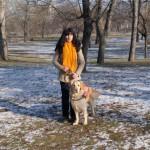 Egy téli erdőben áll egy fiatal hölgy, mellette golden retreiver vakvezető kutyája.