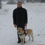 Egy férfi a havas tájon vakvezető kutyájával