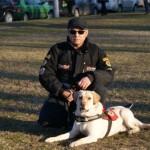 Egy nagy füves terület közepén térdel egy kabátos férfi, mellette a zsemleszínű vakvezető kutyája.