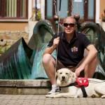 Egy szökőkút peremén egy napszemüveges férfi ül, kezében fehér bot, előtte fekszik a zsemleszínű labrador vakvezető kutyája.
