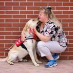 Vörös téglafal előtt egy hölgy guggol és egy zsemleszínű vakvezető kutya ül. A fejüket egymáshoz érintik, mintha a kutya megnyalná a hölgy arcát.