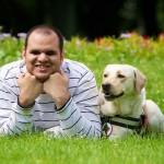 Egy férfi fekszik a mezőn a zöld, virágos fűben. Hozzá egész közel a zsemleszínű labrador vakvezető kutyája.