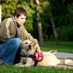 Egy férfi guggol, mellette fekszik zsemleszínű vakvezető kutyája.