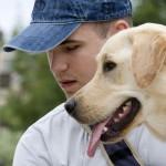 Vakvezető kutya és gazdája: Egy fiatal baseballsapkás férfi feje mellett egy zsemleszínű labrador feje. Egy irányba néznek.