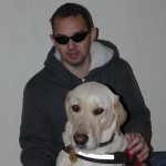 Egy fiatalember, előtte ül a nagytermetű, sárga labrador retreiver vakvezető kutyája.