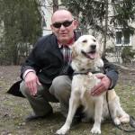 Egy parkban egy idősebb férfi guggol a golden retreiver vakvezető kutyája mellett.