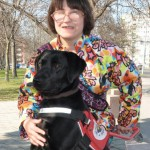 Egy színes mintás ruhában lévő szemüveges hölgy előtt van a fekete labrador vakvezető kutyája, amint mellső lábait épp felteszi egy térelválasztó kőre.