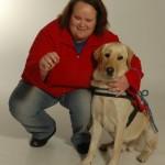 Egy műteremben guggol egy hölgy, mellette zsemleszínű vakvezető kutyája