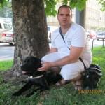 Egy férfi guggol egy fa mellett, előtte fekszik fekete színű vakvezető kutyája.