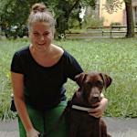 Egy fiatal hölgy letérdelt a vakvezető kutyája mellé a park járdáján, és átöleli a nyakát.