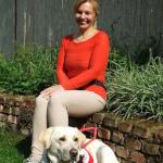 Egy hölgy ül piros felsőrészben egy kövekből épített falmaradványon, előtte fekszik piros hámmal a vakvezető kutyája.