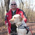 Erdőben egy látássérült és vakvezető kutyája. A kutya egy mohos sziklára teszi fel mellső lábait, így a feje majdnem egy vonalba kerül a gazdi fejével.