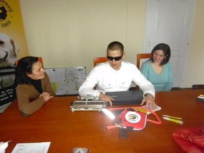 In the picture there is a Braille typewriter, a laptop and a guide dog harness on the table. Two ladies are sitting behind the table with a young man between them.