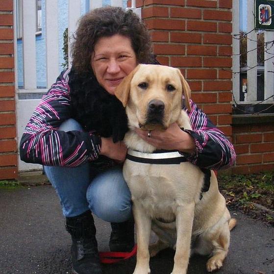 Egy hölgy leguggol és magához öleli vakvezető kutyáját.