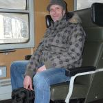 Egy fiatalember ül a vonaton. A két lába között, az ülés alatt fekszik hámban lévő vakvezető kutyája, aki egy fekete labrador.