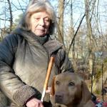 Az erdőben áll egy idős hölgy. Egyik kezében egy fehér botot tart. A másik oldalán áll vakvezető kutyája, egy sárga labrador hámban.
