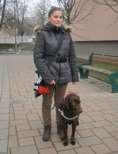 In the picture Debora is standing on the street.  Her chocolate brown labrador is standing on her left.   The dog -lead is her right hand.