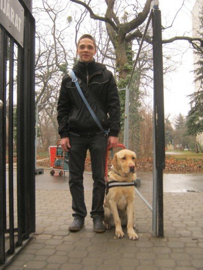 On the picture, Zsolt is standing on the street, his guide dog Andy,who is a Labrador, sits on his left side, wearing her yellow halter. Zsolt is holding the halter with his left hand.