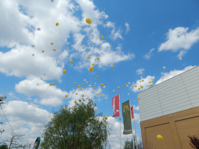 In the picture there are lots of white and yellow balloons in the air.