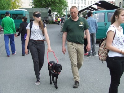 In the picture Delta, a black Labrador in harness, is leading a blindfolded girl. The trainer of Delta is walking beside him.
