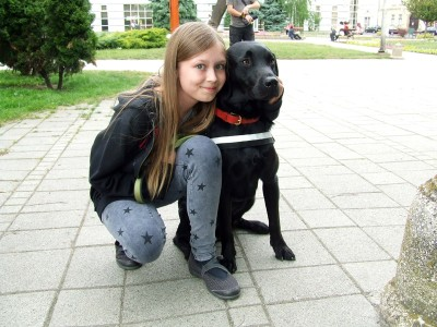 We can see Flash, the black labrador pup-in-training in the picture. A little girl is hugging him.