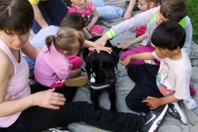 AIn the picture there is a black Labrador lying on a rug. Children are sitting around her caressing her