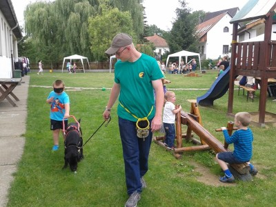 In the picture a Labrador in black harness is leading a blindfolded boy. A man is holding the leash of the dog.