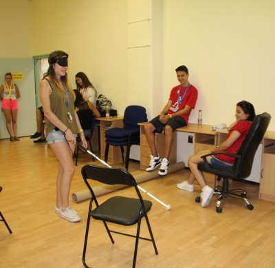 In the picture there is a blindfolded girl walking with a whit cane in a room around different obstacles.