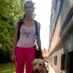 Egy fiatal hölgy áll a keskeny utcán, mellette zsemleszínű vakvezető kutyája.
