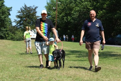 In the picture there is a black Labrador in harness leading a little boy whose hand is being held by his father. The trainer of the dog is walking beside the dog.