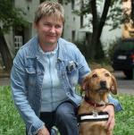 Egy hölgy térdel a vakvezető kutyája mellett, kezét ráteszi.