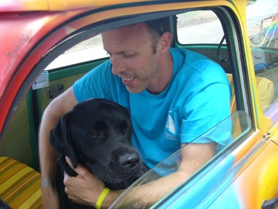 In the picture a young man is sitting in a colourful car, embracing his black Labrador.