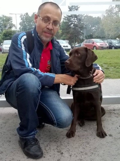 In the picture the owner of a chocolate brown Labrador, who is wearing a harness, is squatting beside the dog and hugging her with his left arm.