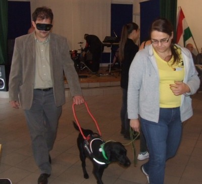 In the picture a black Labradir in harness is guiding a man. The leash of the dog is held by a woman.