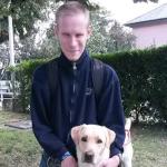 A képen a füvön térdel egy fiatalember és mellette áll vakvezető kutyája, egy sárga hámban lévő labrador. A fiatalember átfogja a kutyát.
