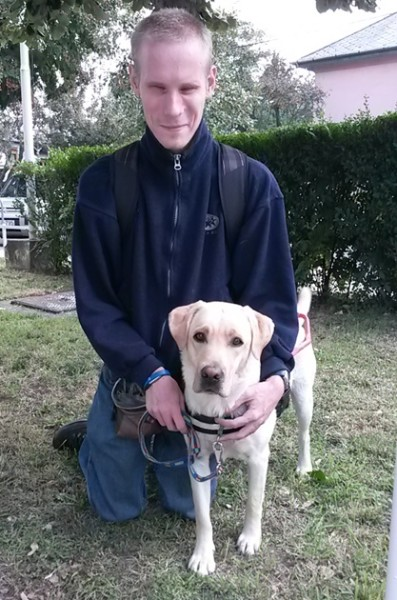 In the picture a young man is kneeling on the grass and his guide dog, a yellow Labrador is standing beside him in harness. The man is embracing the dog.