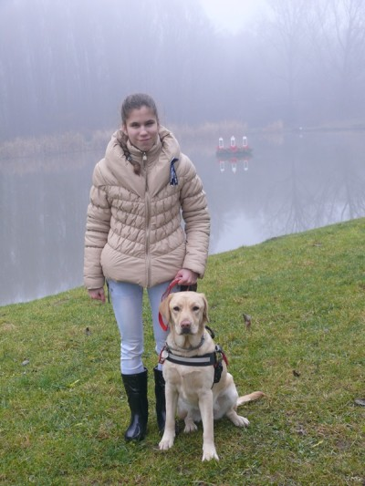 In the picture there is a girl standing in front of a lake and holding the leash of her guide dog, a yellow Labrador.