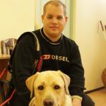 Egy fiatal férfi ül a széken, előtte a zsemleszínű vakvezető kutyája.