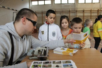 In the picture a boy is reading a brochure in his hand that was being handed over to him by a visually impaired man sitting by the table. Two other pupils are also standing next to the boy.