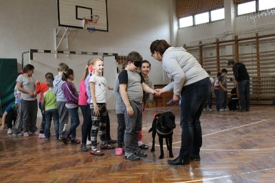 In the picture children are standing in line. The first boy in the row is searching for the harness of the black Labrador standing beside him. The woman standing in front of him helps him by holding his hand.
