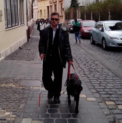 A képen egy férfit vezet fekete vakvezető kutyája az utcán.