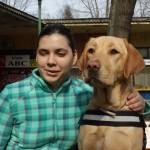 Egy fiatal hölgy a zsemleszínű vakvezető kutyája mellett, fej-fej mellett.