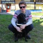 Egy fiatalember guggol , előtte ül a fekete, vékony vakvezető labrador kutyája.