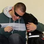 Egy napszemüveges vak fiatalember a hátát a falnak támasztva ül, miközben mellette ülő vakvezető kutyája megnyalja a fülét.