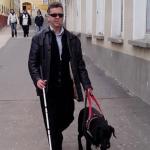 Egy fehér bottal közlekedő feketébe öltözött látássérültet egy fekete vakvezető kutyával halad a sétálóutcán.