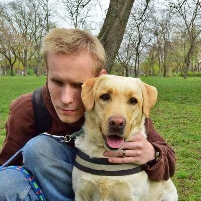 In the picture a young man is kneeling and embracing his yellow Labrador who is wearing a guide dog harness. Halmai Gábor and Gina