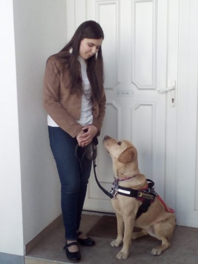In the picture there is a young girl standing in front of a closed white door. She is holding the leash of her guide dog, a yellow Labrador, who is sitting.