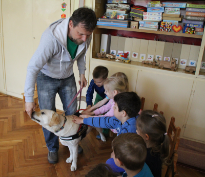 In the picture there are children sitting and stroking a yellow Labrador standing in front of them. The dog is just taking a treat from the trainer.
